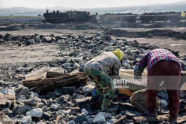 Workers pick up coal from slag on a hill which made by mineral waste residue from 1955 in July 06 Fuxin Liaoning Province China Fuxin is the city...