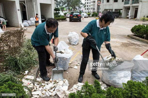 Workers pick up polystyrene and other rubbish in the Heng Fa Chuen area in Hong Kong on August 24 a day after Typhoon Hato created a sea surge which...