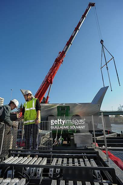 Workers place a hydrokinetic turbine during its installation to a liftable column fixed to a floating barge in the Loire river in Orleans on November...