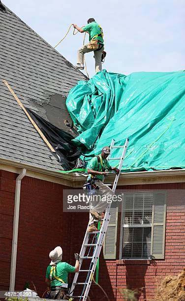 Workers place a tarp on a home that was damaged on Monday by a tornado on May 2 2014 in Tupelo Mississippi People are starting the recovery process...