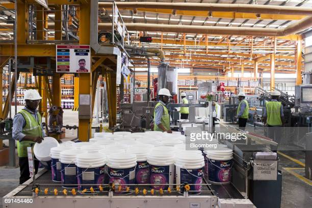 Workers place empty Dulux branded paint buckets onto a filling line at an Akzo Nobel India Ltd factory in Gwalior Madhya Pradesh India on Thursday...