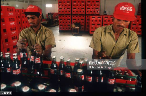 Workers place filled Coca Cola bottles into crates January 27 1994 in India Coca Cola which was banned from India in 1977 to 1978 for failure of...