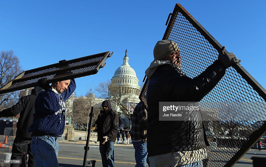 Workers place security fences in place near the Capitol building as the area is prepared for the Presidential inauguration on January 19, 2013 in Washington, DC. The US capital is preparing for the second inauguration of US President Barack Obama, which will take place on January 21.