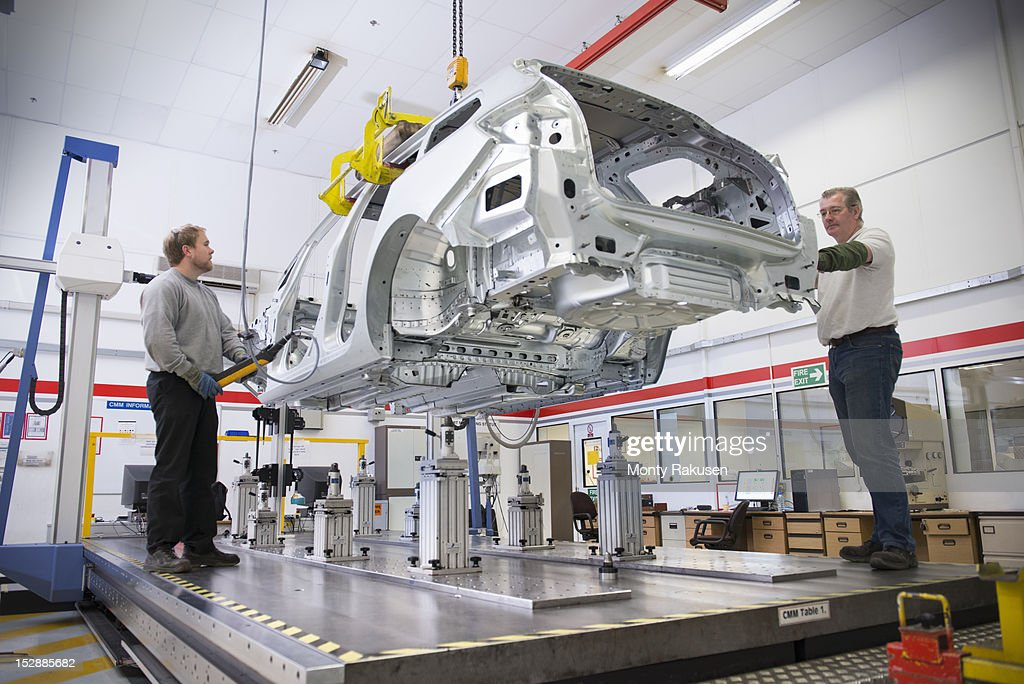 Workers placing car body on measuring machine in car factory