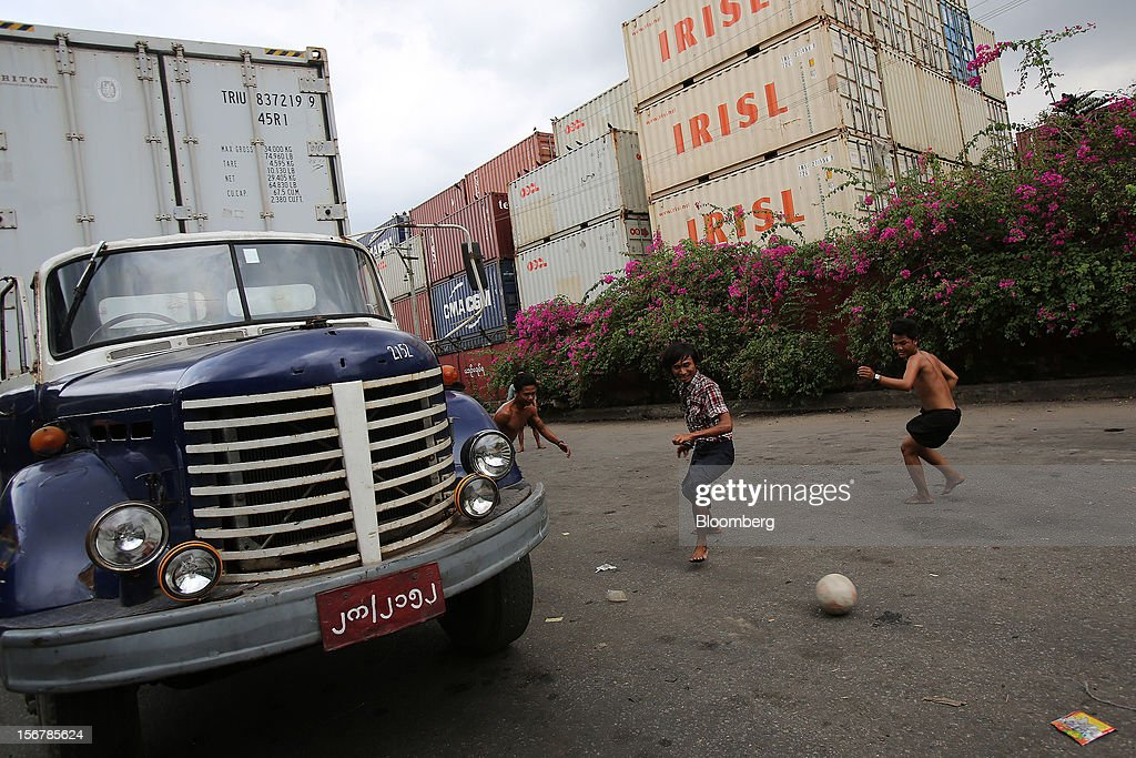 Workers play soccer near a truck at a shipping container depot in Yangon, Myanmar, on Tuesday, Nov. 20, 2012. Myanmar's growth outlook has improved 'substantially' amid political reforms, which are expected to lead to a large influx of foreign investment, the Organization for Economic Cooperation and Development (OECD) said on Nov. 18. Photographer: Dario Pignatelli/Bloomberg via Getty Images