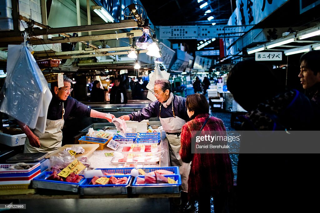 Workers point to a fish as they serve a customer at the Tsukiji fish market on February 28 2012 in Tokyo Japan Handling nearly 3000 tons of fish a...
