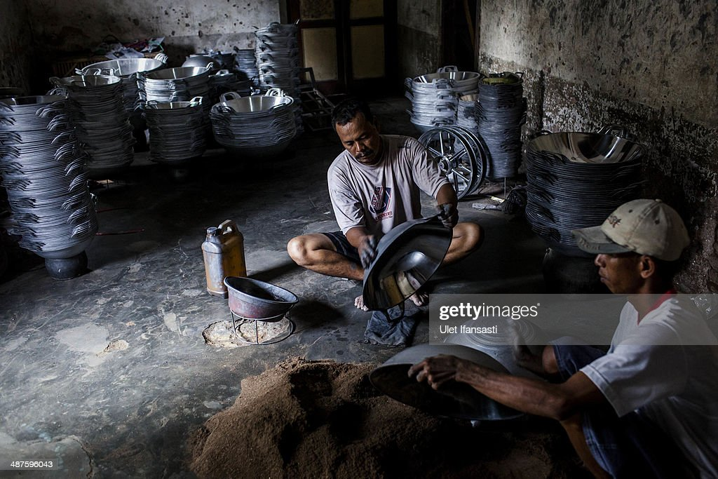 Workers polish a pan at Putra Logam workshop on May 1, 2014 in Yogyakarta, Indonesia. The pan polishers are paid around Rp. 40.000 (USD 3.46) per day. Today is International Labour Day, which aims to bring attention to working conditions, higher wages, and working hours across the world. Protesters across Indonesia have organised rallies to demand higher wages, as Indonesia recognises its first national labour day holiday.
