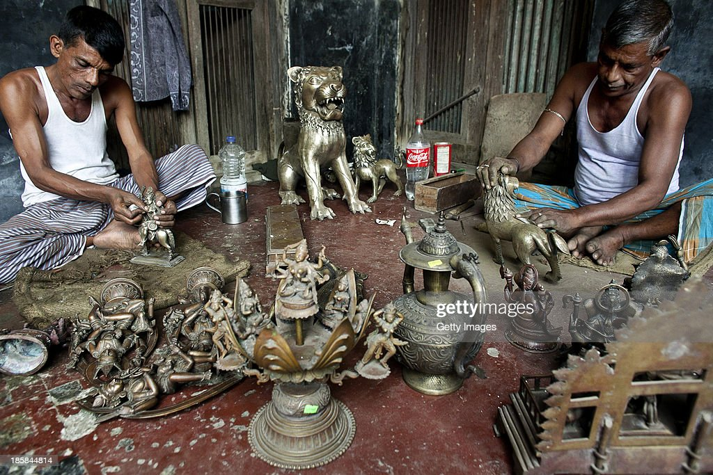 Workers polish sculptures at Dhamrai Metal Crafts on October 5, 2013 in Dhaka, Bangladesh. The owner of the metal crafts shop, Sukanta Banik, creates bronze sculptures in the art of 'lost wax casting.' The business has been in his family for 200 years. The pieces are first molded in wax, then encased in clay, then baked in the oven, after which metal is poured into the mold. One piece can take up to 10 months to make. The business is suffering because most of these items he creates can now be mass produced in plastic, and as a Hindu artist working in Islamic Bangladesh, the 'depiction of all humans and animals are discouraged by the majority religion.' Recently it took a year and a half to send an order overseas, when Bangladeshi customs held his work in hopes for a bribe.