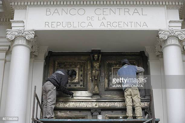 Workers polish the back doors of Argentina's Central Bank in Buenos Aires on September 9 2008 Argentina had announced on September 2 it will pay off...