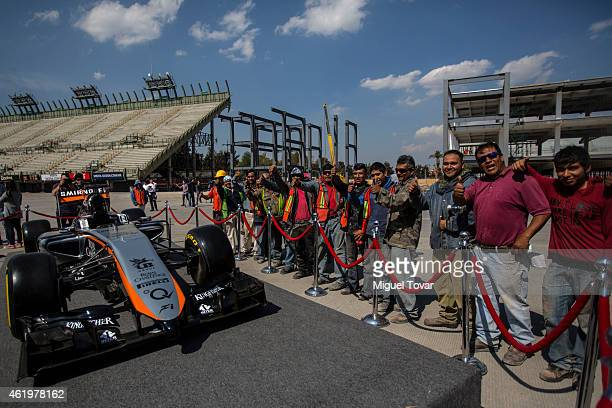 Workers pose for pictures next to the F1Team Force's India new car at the Hermanos Rodriguez Racing Circuit Facilities on January 22 2015 in Mexico...