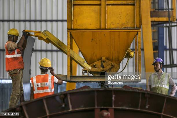 Workers pour concrete from a kibble into a mold of precast concrete tunnel segment at the Mumbai Metro Rail Corp casting yard in Mumbai India on...