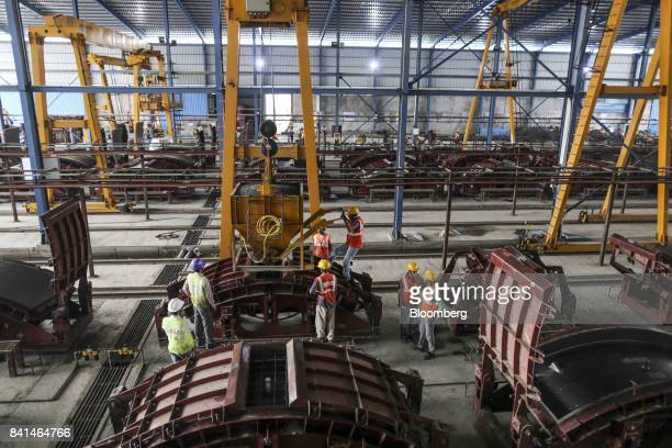 Workers pour concrete from a kibble into the mold of a precast concrete tunnel segment at the Mumbai Metro Rail Corp casting yard in Mumbai India on...