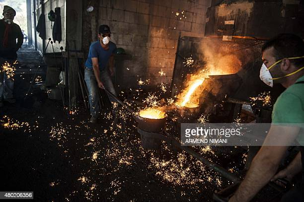 Workers pour molten metal after seized weapons were destroyed at a metal foundry near the village of Janjevo on July 9 2015 Around 1800 weapons were...
