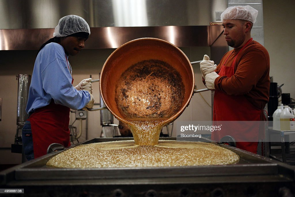 Workers pour out a kettle of cooked corn syrup to be made into candy canes at the Hammond's Candies production facility in Denver Colorado US on...