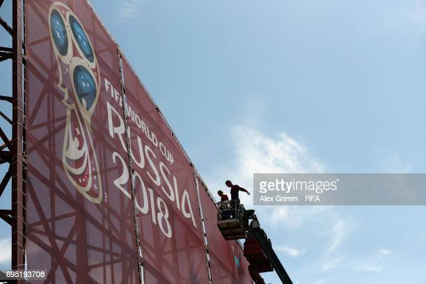 Workers prepare a banner in the Olympic Park ahead of the FIFA Confederations Cup Russia 2017 on June 12 2017 in Sochi Russia