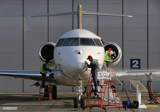 Workers prepare a Bombardier Inc Global 6000 aircraft ahead of the Jet Expo 2012 exhibition at Vnukovo airport in Moscow Russia on Thursday Sept 27...