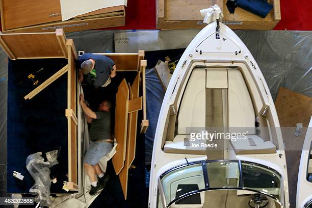 Workers prepare a display for the opening of The 2015 Miami International Boat Show on February 11 2015 in Miami Beach Florida The boat show starts...