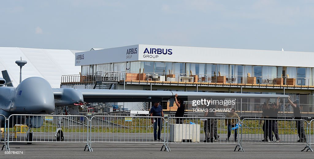 Workers prepare a 'Heron' drone at the International Aerospace Exhibition (ILA) in Schoenefeld on May 30, 2016. The Aerospace Exhibition at Schoenefeld Airport near Berlin takes place from June 1 till 4. / AFP / TOBIAS