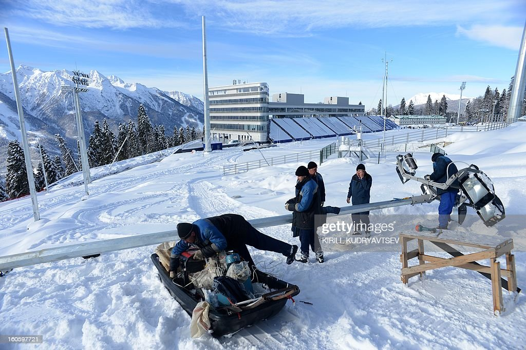 A workers prepare a lamp on the shooting range of the Laura Cross Country and Biathlon Center in Russian Black Sea resort of Sochi on February 3, 2013.
