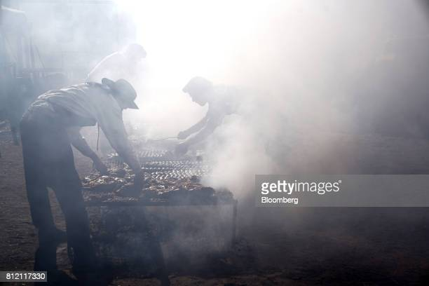 Workers prepare a traditional asado during the AgroActiva fair in Armstrong Santa Fe Argentina on Thursday June 1 2017 YPF SA the staterun oil...