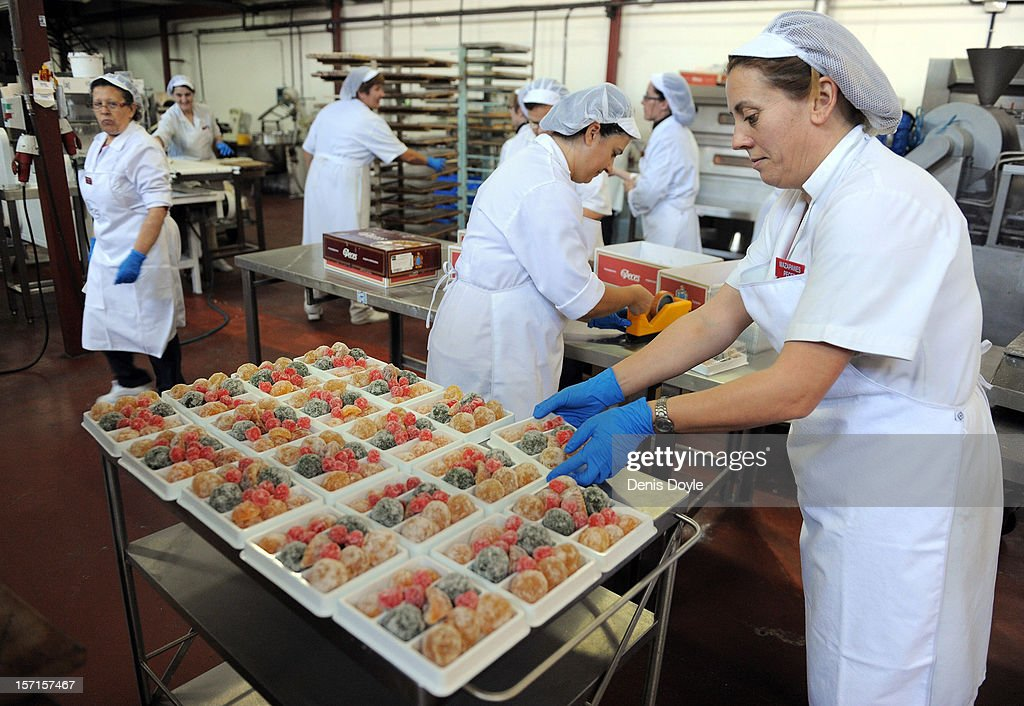 Workers prepare a tray of traditional 'frutas escarchada' at the Peces Mazapanes bakery on November 28, 2012 in the town of Consuegra, near Toledo, Spain. The company opens annually during the three months leading up to christmas hiring 32 workers to produce traditional Spanish christmas cakes called Mazapanes.