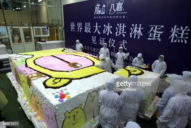 Workers prepare an ice cream cake with the major character image of a children's play Magic Mountain' as the cover during a promotional event at a...