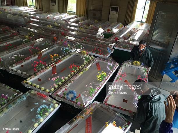 Workers prepare coffins for victims from the capsized ship Dongfangzhixing at a funeral parlour on June 3 2015 in Jingzhou China A passenger ship...