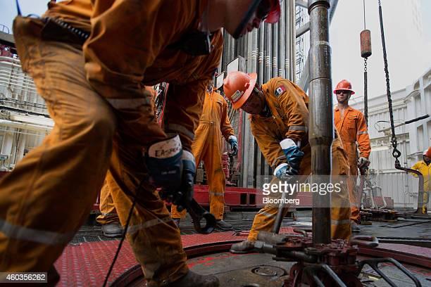 Workers prepare drilling pipe on the Petroleos Mexicanos La Muralla IV deep sea crude oil platform in the waters off Veracruz Mexico on Friday Aug 30...