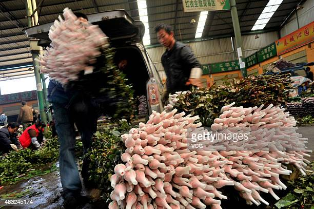 Workers prepare flower bouquets for the upcoming Valentine's Day at a flower market on February 12 2015 in Kunming Yunnan province of China
