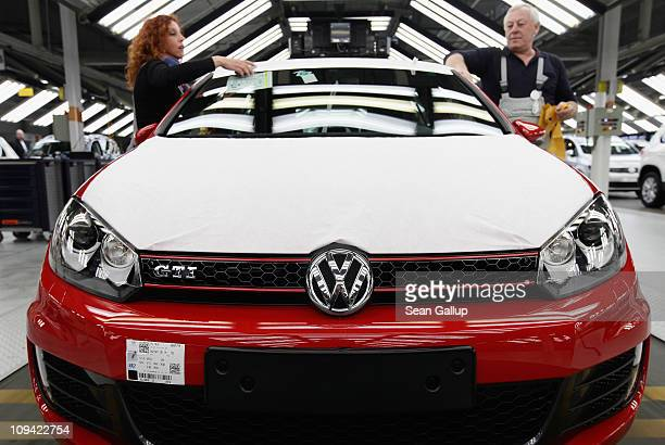 Workers prepare new Volkswagen Golf 6 cars at the Volkswagen factory on February 25 2011 in Wolfsburg Germany Volkswagen and other German carmakers...