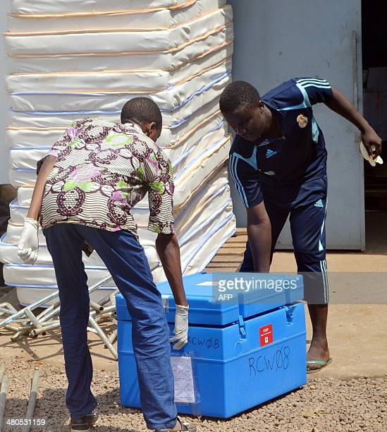 Workers prepare on March 25 2014 at a warehouse of the Swiss branch of the NGO Medecins sans Frontieres in Conakry protection material to be used on...
