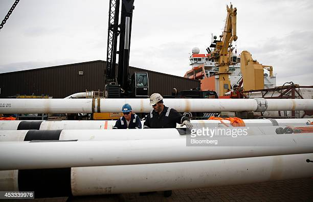 Workers prepare pipes destined for the Clair Ridge oil and gas field off the Shetland Isles before loading onto the Normand Oceanic offshore supply...
