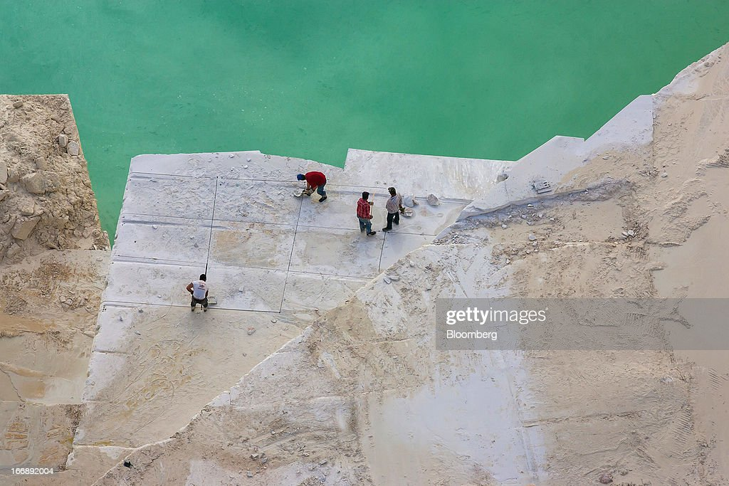 Workers prepare raw marble for cutting beside a pool of rainwater inside a quarry pit operated by Bloco B in Pardais, Vila Vicosa, Portugal, on Wednesday, April 17, 2013. Portugal is posting its first trade surplus in at least six decades, which may help vindicate a strategy of front-loading austerity to deliver economic reform. Photographer: Mario Proenca/Bloomberg via Getty Images