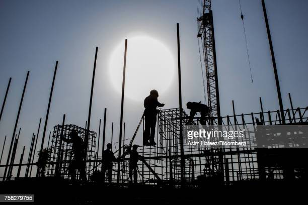 Workers prepare reinforcing steel at a construction site.