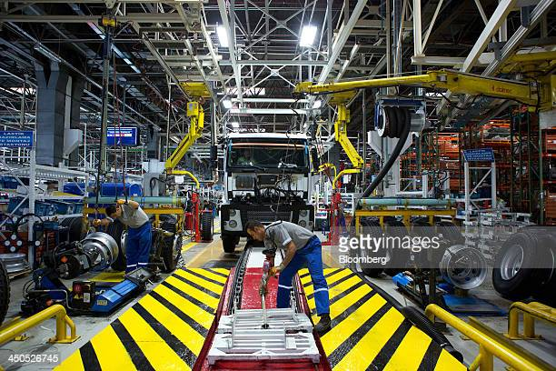 Workers prepare the bay before attaching wheels and tires to a Ford Cargo truck on the production line at Ford Otosan the joint venture between Ford...
