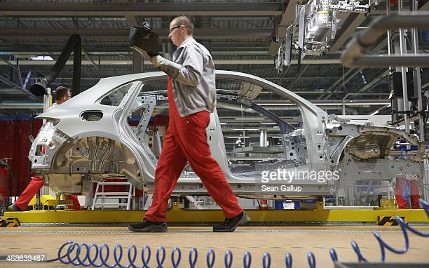 Workers prepare the body of a Porsche Macan SUV at the new Porsche Macan factory at the Porsche plant on February 11 2014 in Leipzig Germany Porsche...