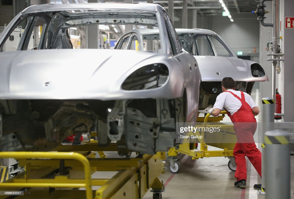 Workers prepare the body of a Porsche Macan SUV at the new Porsche Macan factory at the Porsche plant on February 11, 2014 in Leipzig, Germany. Porsche plans to produce 50,000 of the new small SUV Macan annually.