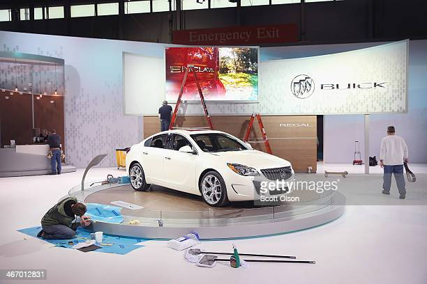 Workers prepare the Buick exhibit at the Chicago Auto Show on February 5 2014 in Chicago Illinois The show which is held at McCormick Place runs...