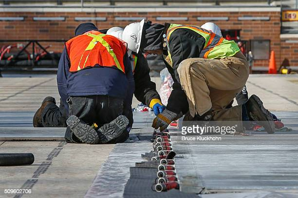 Workers prepare the field to build a rink at TCF Bank Stadium on February 11 2016 in Minneapolis Minnesota The field will be the site of the 2016...