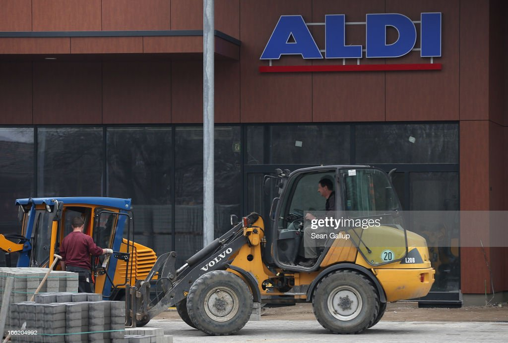 Workers prepare the future parking lot in front of a new Aldi Nord discount supermarket on the 100th anniversary of the chain on April 10, 2013 in Berlin, Germany. Aldi, which today is among the world's most successful discount grocery store chains, will soon mark its 100th anniversary and traces its history back to Karl Albrecht, who began selling baked goods in Essen on April 10, 1913 and founded the Aldi name by shortening the phrase Albrecht Discount. His sons Karl Jr. and Theo expanded the chain dramatically, creating 300 stores by 1960 divided between northern and southern Germany, with Aldi Nord and Aldi Sued, respectively. Today the two chains have approximately 4,300 stores nationwide and have also expanded into other countries across Europe and the USA. Aldi Nord operates in the USA under the name Trader Joe's.
