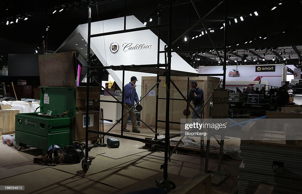 Workers prepare the General Motors Co. Cadillac exhibit during an advance tour of the North American International Auto Show (NAIAS) at Cobo Hall in Detroit, Michigan, U.S., on Thursday, Jan. 10, 2013. More than 23,000 attendees representing almost 2,000 companies are expected to attend the industry preview for NAIAS on Jan. 16-17. The general public can attend the show from Jan. 19-27. Photographer: Jeff Kowalsky/Bloomberg via Getty Images