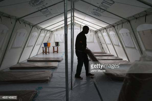 Workers prepare the new Doctors Without Borders Ebola treatment center on August 17 2014 near Monrovia Liberia The facility initially has 120 beds...