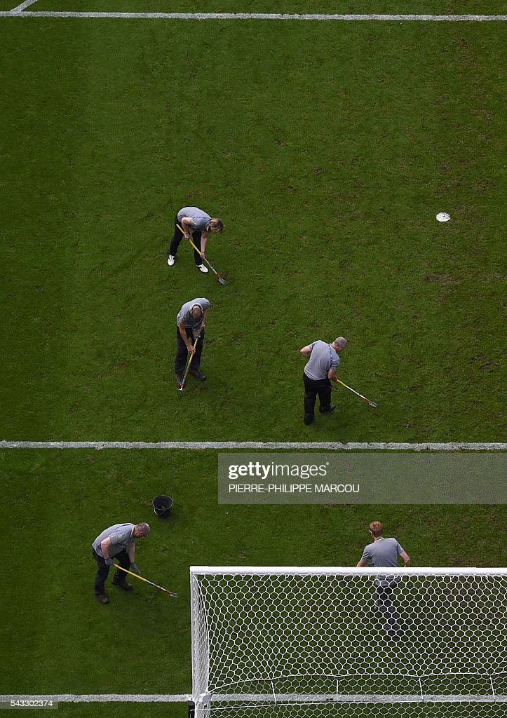 Workers prepare the pitch during the half time of the Euro 2016 round of 16 football match between Italy and Spain at the Stade de France stadium in Saint-Denis, near Paris, on June 27, 2016. / AFP / Pierre-Philippe MARCOU