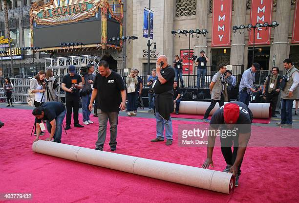 Workers prepare the red carpet at the 87th Annual Academy Awards red carpet installation photo op held at Hollywood Highland Center on February 18...