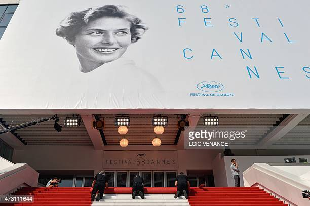 Workers prepare the red carpet at the Festival palace ahead of the opening of the 68th Cannes Film Festival in Cannes southeastern France on May 13...