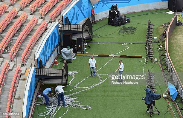 Workers prepare the stadium at the Arena Amazonia on June 12 2014 in Manaus Brazil England play Italy in their group opening match on Saturday 14th...
