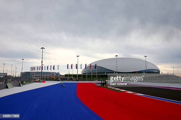 Workers prepare the track next to the Bolshoi Ice Dome during previews ahead of the Russian Formula One Grand Prix at Sochi Autodrom on October 8...