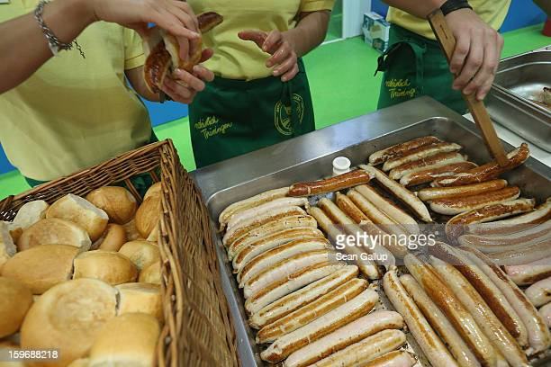 Workers prepare Thuringian bratwurst sausages at the 2013 Gruene Woche agricultural trade fair on January 18 2013 in Berlin Germany The Gruene Woche...