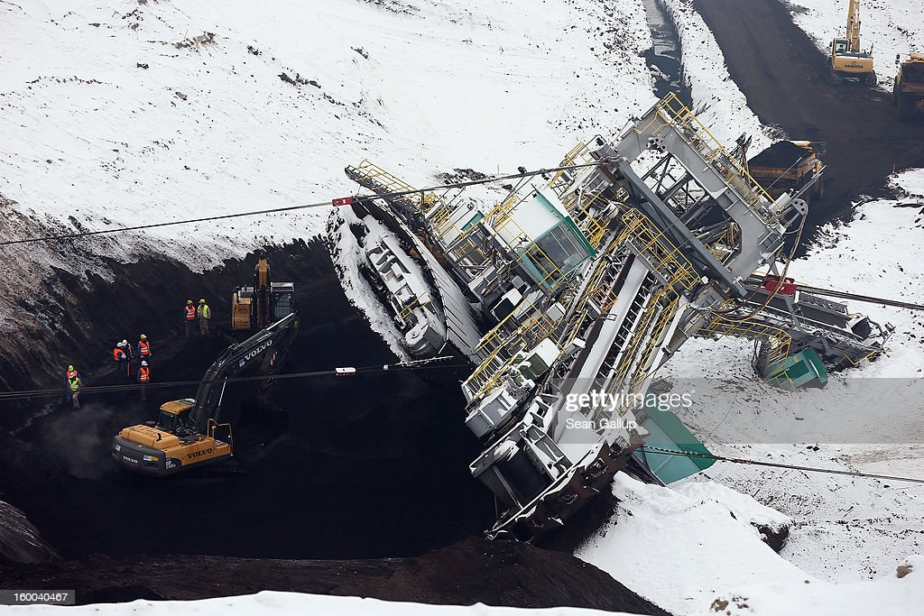 Workers prepare to attempt to set a 950-tonne bucket excavator upright following an accident at an open-pit coal mine on January 25, 2013 near Deutzen, Germany. The bucket excavator tipped over last summer after plateaus of earth and sand nearby gave way, pushing a layer of coal underneath. The excavator has been lying severaly tilted to one side ever since at the Vereinigtes Schleenhain mine, which is operated by Mibrag. Open-pit lignite coal mines are still common across eastern Germany and produce coal for local electricity production.