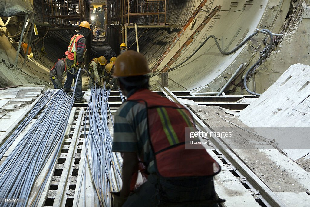 Workers prepare to carry the steel rods inside the Tunnel Emisor Oriente (TEO), or Eastern Discharge Tunnel, during construction of the 38 mile (62km) underground wastewater treatment tunnel in Mexico City, Mexico, on Thursday, Sept. 12, 2013. The tunnel, which is expected to be completed in 2014, will boost Mexico City's drainage capacity to help prevent flooding during rainy season and the over-exploitation of groundwater resources. The project is being managed by Mexico's National Water Commission, Conagua. Photographer: Susana Gonzalez/Bloomberg via Getty Images